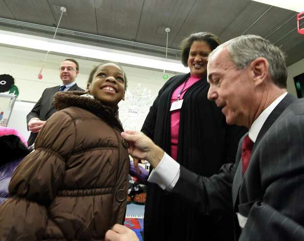 Sporting a big smile and a new coat is Trinity Morrison of Arbor Hill Elementary School, left as Albany School Superintendent Dr. Marguerite Vanden Wyngaard, cents rand Devils CEO Chris Ciceri assist with the fitting during the press conference announcing the results of the Cash for Coats program in Albany, N.Y.     (Skip Dickstein/Times Union) Photo: SKIP DICKSTEIN / 00029576A