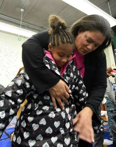 Soleil Caldwell, student at the Arbor Hill Elementary School is fitted for a new winter coat by Albany School Superintendent Dr. Marguerite Vanden Wyngarard during the press conference announcing the results of the Cash for Coats program in Albany, N.Y.     (Skip Dickstein/Times Union) Photo: SKIP DICKSTEIN / 00029576A