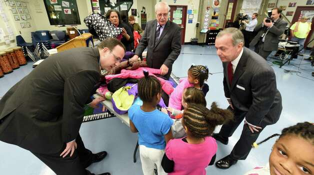 Students from the Arbor Hill Elementary School are fitted for a new winter coat by Jack Yonally, center rear, of Lodge's Department Store, Mark Yonally, left and Albany Devils CEO Chris Ciceri, right, during the press conference announcing the results of the Cash for Coats program in Albany, N.Y.     (Skip Dickstein/Times Union) Photo: SKIP DICKSTEIN / 00029576A