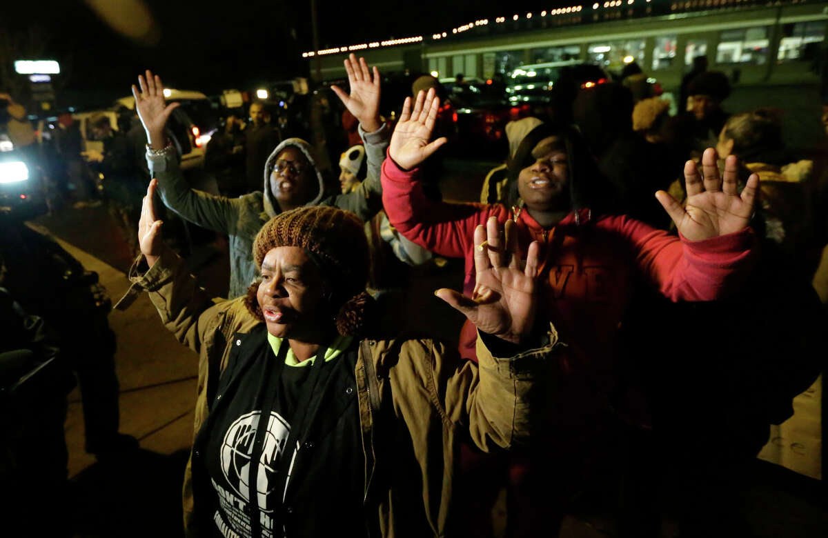 Barbara Jones and protesters raise hands in Ferguson, Mo., as they await the grand jury decision in the Michael Brown killing.