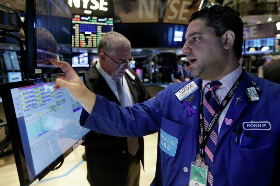 Specialists work their post on the floor of the New York Stock Exchange. Mounting signs of weakness in the global economy and a poor start to the holiday shopping season knocked the stock market lower on Monday  (AP Photo/Richard Drew) ORG XMIT: NYRD102 Photo: Richard Drew / AP