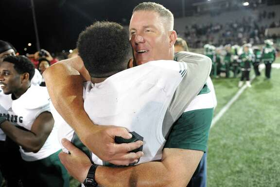 Spring coach Sam Parker, right, hugs linebacker Miles Johnson after the Lions' 41-16 victory over Klein Oak on Nov. 6 put Spring into the playoffs for the first time since 2004. The Lions, one of four District 15-6A teams in the playoffs, have advanced to the regional semifinals, along with Klein Oak, Klein Collins and Westfield.