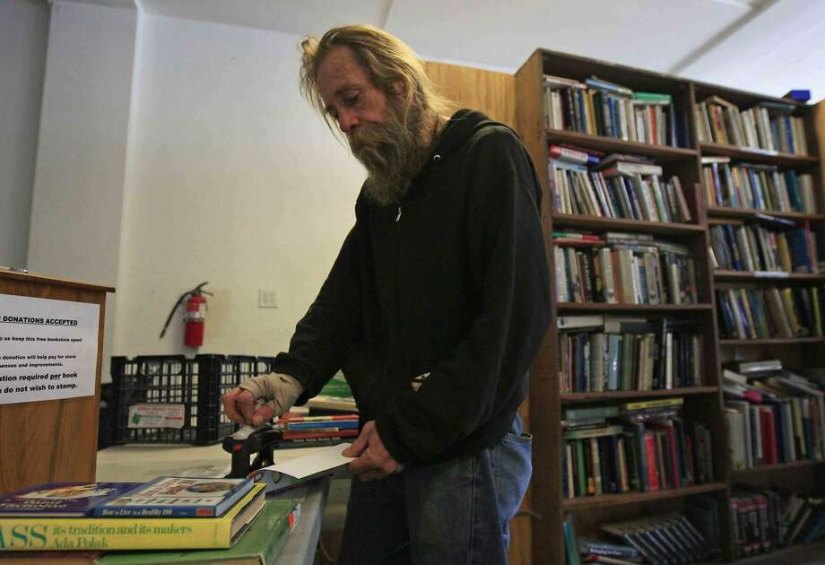 Gunther Williams of El Sobrante stamps his books, marking them so they may not be re-sold, at the Bay Area Free Book Exchange on San Pablo Avenue in El Cerrito. Photo: Jessica Christian, The Chronicle