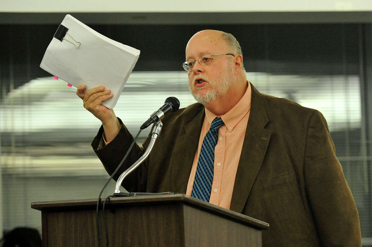 Jim Cameron, head of the Commuter Action Group, displays the state's request for proposal as he speaks during the public hearing in front of the Zoning Board on the proposed redevelopment of the Stamford train station parking garage at the Stamford Government Center in Stamford, Conn., on Monday, Nov. 24, 2014. The state Department of Transportation picked John McClutchy to develop the current train station parking garage into a $500 million, 1 million square feet mixed-use property. Many speakers were concerned about the low number of spaces, safety and the distance commuters must travel from their parking spaces to the train platform.