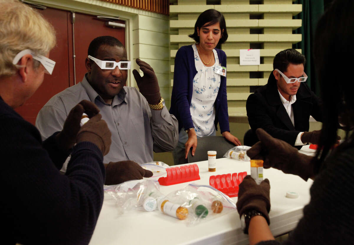 UCSF Geriatrician Meera Sheffrin, MD, center, jokes with San Francisco Police officers, from left, Will Ahern, Jabari Jackson, Jeff Chow and Tina Galande while they attempt to fill prescriptions with vision impairing glasses at the vision loss and medication management station during a Crisis Intervention Training course at the County Fair Building Nov. 19, 2014 in San Francisco, Calif. The exercises were part of a training developed by UCSF designed simulate issues that may come up with the elderly population to help the officers better understand what they may be going through.