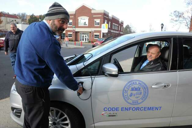 Treasurer Peter Frangie, left, and Cohoes Mayor George Primeau check out the new vehicles during the announcement of the acquisition of the 2 Ford C-Max Electric Cars to be assigned to code enforcement on Friday Nov. 21, 2014 in Cohoes, N.Y. (Michael P. Farrell/Times Union) Photo: Michael P. Farrell / 00029585A