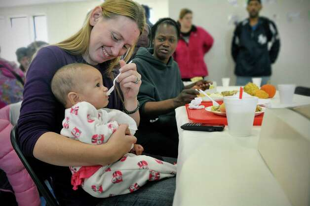 Jennifer Shatraw of Albany feeds her daughter, Sophia Smith, 5 months, some mashed potatoes as Sophia's aunt Lola Smith, also of Albany, looks on  during a Thanksgiving lunch hosted by Mazzone Hospitality at the  Sister Maureen Joyce Center on Monday, Nov. 24, 2014, in Albany, N.Y.  The center is a soup kitchen in the West Hills area of Albany that feeds lunch to area residents on Sunday, Monday and Thursday.  The center feeds roughly 900 meals a month.  The center is run through a partnership with Catholic Charities of the Diocese of Albany, Blessed Sacrament Church, Congregation Beth Emeth, and The Ladies of Charity.  This is the first year that Mazzone Hospitality hosted the Thanksgiving lunch.  (Paul Buckowski / Times Union) Photo: Paul Buckowski / 00029570A