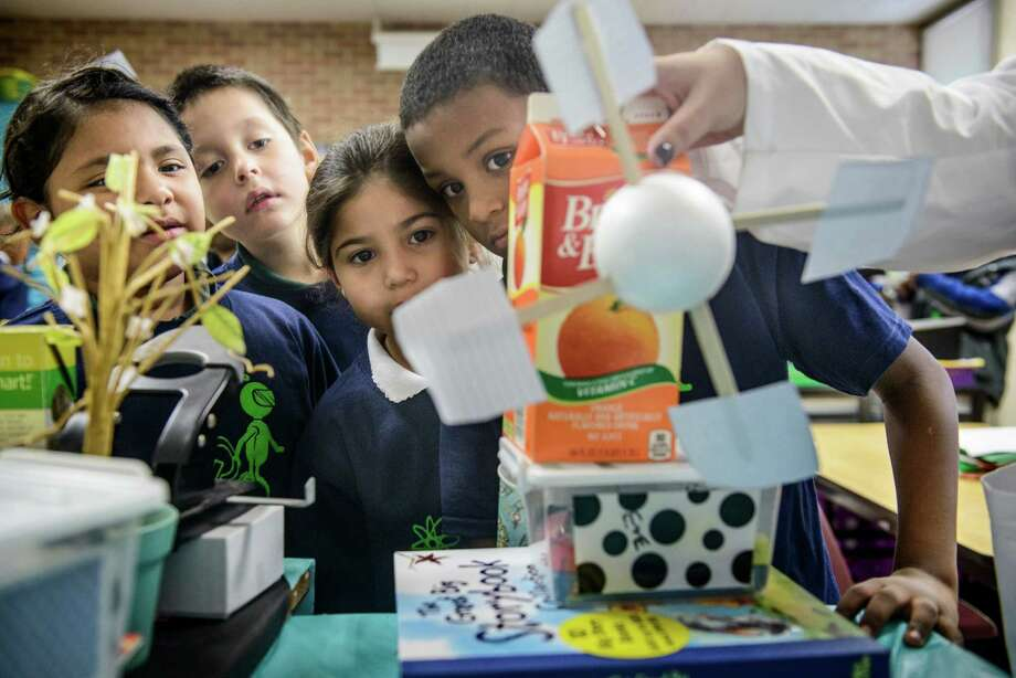 From left, first grade students Diamond Marie, Jonathan Riley, Belen Viesca and Eugene Solomon watch as their windmill is tested using a small fan during engineering Fridays at Pershing Elementary School in San Antonio, Tx. on Thursday, November 20, 2014. The students were tasked with building a windmill that would lift washers attached to the back side of the cartons. East Side schools that fall into the Promise grant footprint are incorporating engineering lessons into their curriculum as a way to boost critical thinking skills and an interest in science. Photo: Matthew Busch / Matthew Busch / For The San Antonio Express-News / © San Antonio Express-News