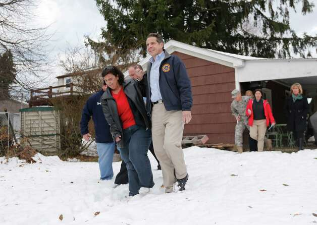 New York Gov. Andrew Cuomo, right, helps resident Nancy Barletta through the snow at her house while surveying the aftermath of last week's lake-effect snowstorms on Monday, Nov. 24, 2014, in West Seneca, N.Y. (AP Photo/Mike Groll) ORG XMIT: NYMG108 Photo: Mike Groll / AP