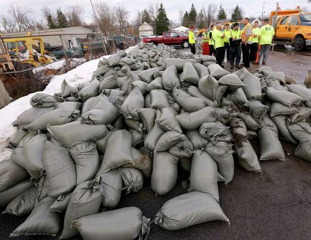 Workers wait for pallets to load sand bags at the West Seneca Highway Department, Monday, Nov. 24, 2014, in West Seneca, N.Y., that were prepared for deployment for potential flooding after last week's heavy snows.  (AP Photo/Mike Groll) ORG XMIT: NYMG105 Photo: Mike Groll / AP