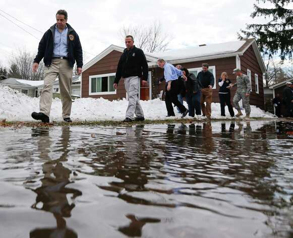 New York Gov. Andrew Cuomo, left, walks along a watery driveway while surveying the aftermath of last week's lake-effect snowstorms on Monday, Nov. 24, 2014, in West Seneca, N.Y. (AP Photo/Mike Groll) ORG XMIT: NYMG111 Photo: Mike Groll / AP