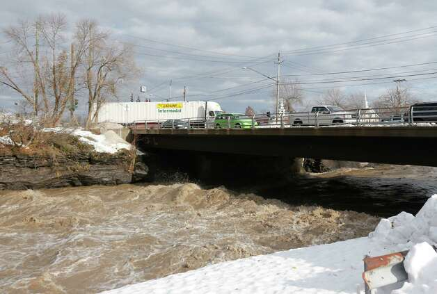 Traffic drives over the Buffalo Creek on Union Road on Monday, Nov. 24, 2014, in West Seneca, N.Y. Western New York is preparing for potential flooding from melting snow after last week's heavy snowstorms. (AP Photo/Mike Groll) ORG XMIT: NYMG104 Photo: Mike Groll / AP