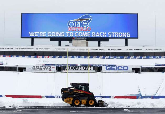 "Workers clear snow from the field at Ralph Wilson Stadium on Sunday, Nov. 23, 2014, in Orchard Park, N.Y. Snowed out today at the stadium, the Bills are in Detroit to play their ""home"" NFL football game against the New York Jets on Monday night, Nov. 24, 2014. (AP Photo/Mike Groll) ORG XMIT: NYMG109 Photo: Mike Groll / AP"