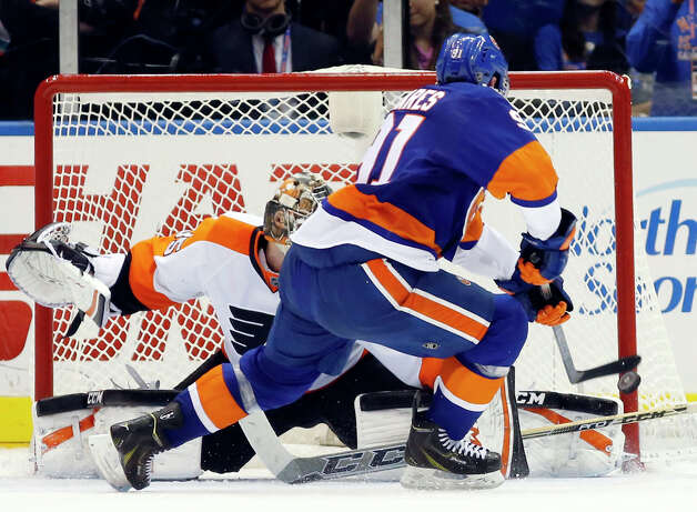 New York Islanders center John Tavares (91) scores a goal in a shootout against the Philadelphia Flyers goalie Steve Mason (35) in an NHL hockey game at Nassau Coliseum in Uniondale, N.Y., Monday, Nov. 24, 2014. The Islanders won 1-0 in a shootout. (AP Photo/Kathy Willens) ORG XMIT: UNI110 Photo: Kathy Willens / AP