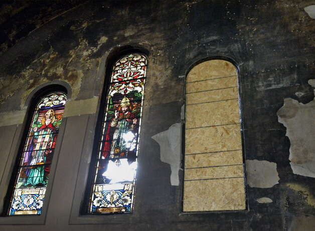 In this photograph taken on May 16, 2014, fire damage can be seen in the stained-glass windows above the altar in the sanctuary of St. Anthony's Church in Schenectady, NY. (John Carl D'Annibale / Times Union)   John Carl D'Annibale