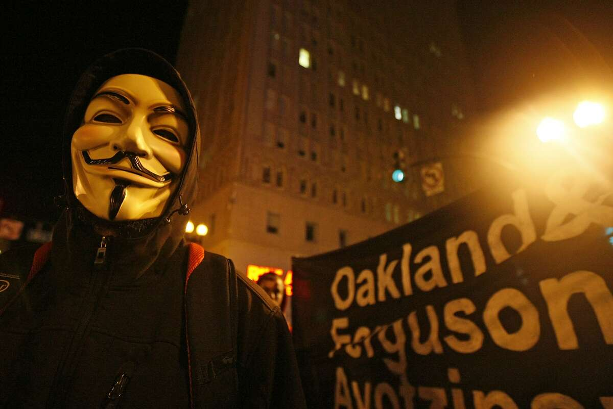 A protester wearing an Anonymous mask stands in the intersection of 14th and Broadway Monday, November 24, 2014 in Oakland, Calif. during protest following the announcement of the no indictment verdict of Darren Wilson in the Mike Brown shooting in Ferguson, Missouri.