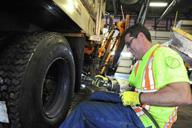 Truck operator Bob Heaphy puts fresh tires on a plow for the winter season at the DOT highway facility off Exit 5 on Monday, Nov. 24, 2014 in Latham, N.Y. The Capital Region is expected to get hit with a snow storm on Wednesday.  (Lori Van Buren / Times Union) Photo: Lori Van Buren / 00029615A