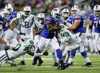 Buffalo Bills running back Anthony Dixon pulls away from the New York Jets defense for a 30-yard touchdown during the second half of an NFL football game in Detroit, Monday, Nov.24, 2014. (AP Photo/Rick Osentoski) ORG XMIT: DTF132