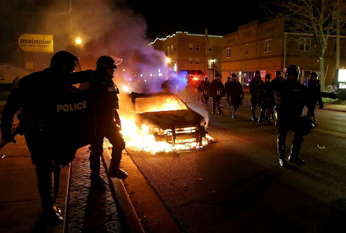 FERGUSON, MO - NOVEMBER 24: Police officers walk by a burning police car during a demonstration on November 24, 2014 in Ferguson, Missouri. A St. Louis County grand jury has decided to not indict Ferguson police Officer Darren Wilson in the shooting death of Michael Brown that sparked riots in Ferguson, Missouri in August. (Photo by Justin Sullivan/Getty Images)
