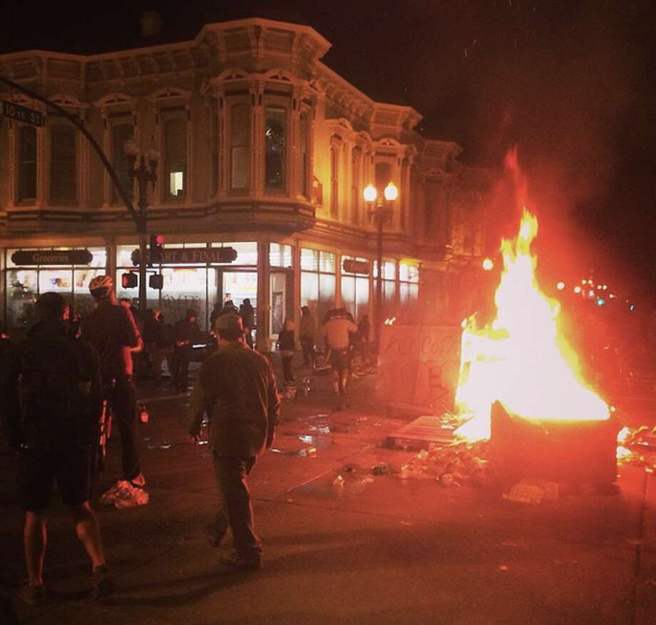 A fire burns in the middle of the street in front of a building being looted by protesters in downtown Oakland early on Tuesday, Nov. 25, 2014. Photo: Leah Millis, Chronicle