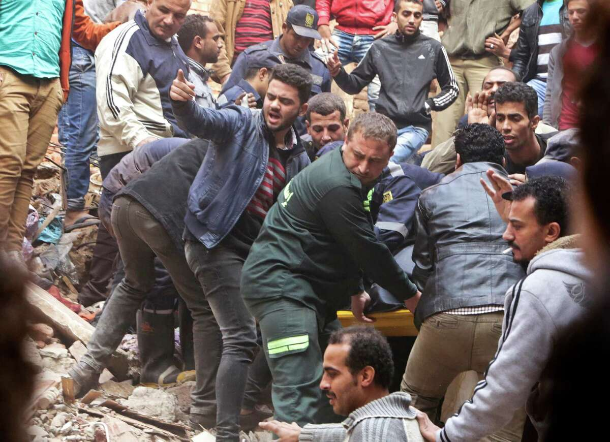 Egyptian volunteers and rescuers carry the body of a victim in the rubble of a building that collapsed in the Cairo suburb of Matariya, early Tuesday, Nov. 25, 2014. Police officials say several people were killed. Building collapses are common in Egypt, where shoddy construction is widespread in shantytowns, poor city neighbourhoods and rural areas.