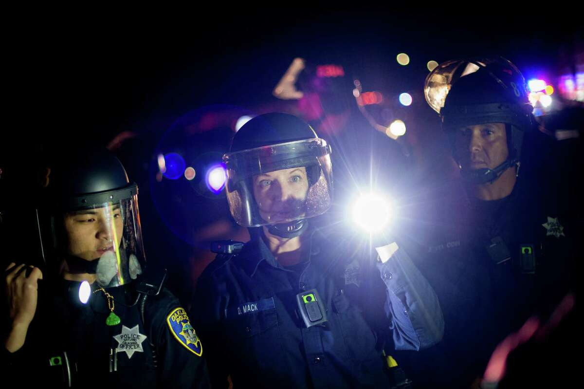 Police officers try to clear demonstrators blocking Interstate 580 in Oakland, Calif., on Monday, Nov. 24, 2014, after the announcement of the grand jury decision not to indict Ferguson police officer Darren Wilson in the fatal shooting of Michael Brown, an unarmed 18-year-old.