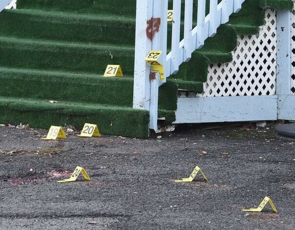Evidence markers cover the ground and steps outside a Bridge Street, Schenectady home on Tuesday, Nov. 25, 2014, the day after a man was shot dead and another gravely injured in a stabbing on the Mont Pleasant Street. (Skip Dickstein / Times Union)