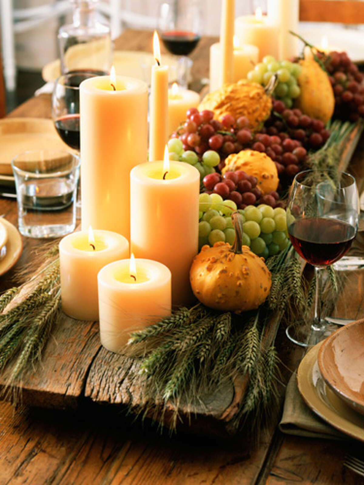 White Pillar Candles Arrange a large group of scentless white pillar candles in various heights on a large wooden tray in the center of your dining table. Add wheat stalks, fresh fruit, and gourds for an extra festive display. The Best Thanksgiving Turkey RecipesRecipes for Thanksgiving LeftoversDelicious Thanksgiving DessertsThe Best Thanksgiving PiesFresh Thanksgiving Table IdeasCozy Ways To Decorate For Fall