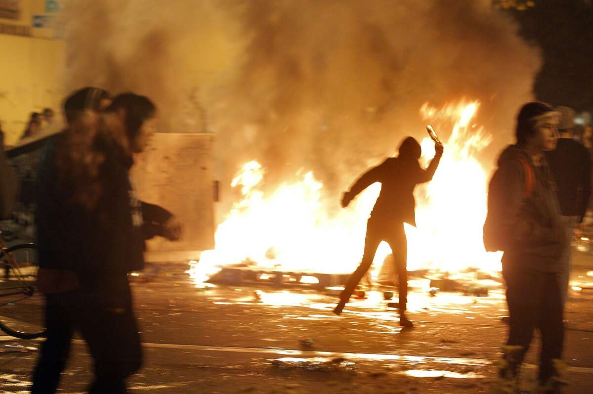 Protesters walk by and hurl things into a trash fire on Broadway in Oakland, Calif. Monday, November 24, 2014 during a protest following the announcement of no indictment against the officer who shot and killed Michael Brown in Ferguson, Missouri.
