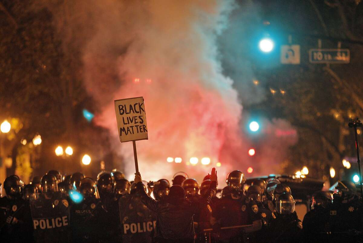 """A protester holds a sign reading, """"Black Lives Matter,"""" in front of a line of police officers in Oakland, Calif., on Monday, November 24, 2014, during a protest following the announcement of no indictment against the officer who shot and killed Michael Brown in Ferguson, Missouri."""