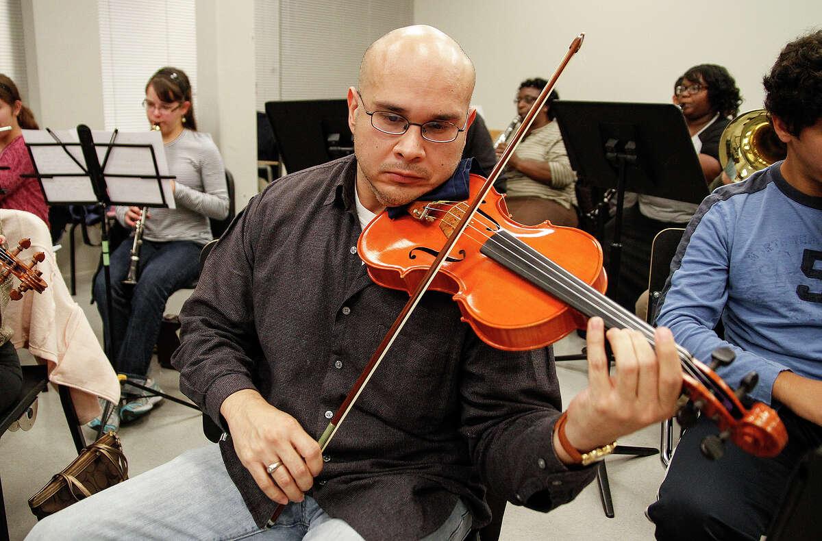 Darren Garza plays the violin at the rehearsal.