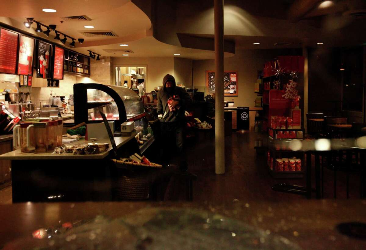 A protester loots a Starbucks on 8th and Broadway during a protest against the grand jury's decision not to indict the white police officer who fatally shot an unarmed black teenager months ago in Ferguson Nov. 24, 2014 in Oakland, Calif.