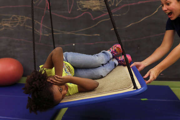 Brittany Morgan, right, ABA Therapist, works with a client at the Autism Treatment Center, Thursday, Nov. 6, 2014. The swing was part of the childÕs reward after a lesson. Autism Treatment Center is San Antonio's first, and only provider of autism services that meet the needs of individuals at every stage of life. Founded in 1976, the agency has grown with the expanding needs of the San Antonio children, families and adults who have struggled to understand and overcome the challenges autism presents. There are 75 employees and a $5 million budget to provide services including early diagnosis and therapy for children, a special TEA certified school, adult vocational training, and residential homes.