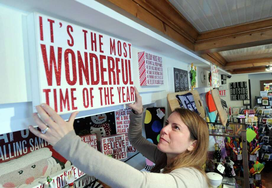 Sonia Sotire Malloy, owner of the Splurge store, hangs one of the catch-phrase signs that the store is known for inside the store at 39 Lewis Street, Greenwich, Wednesday, Nov. 20, 2013. Photo: Bob Luckey / Greenwich Time
