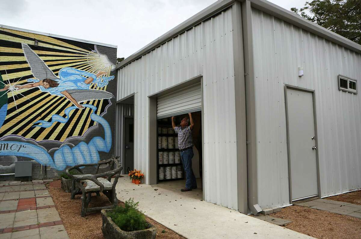 Harvey Mireles, Director of San Anto Cultural Arts, opens a large door at the new building at San Anto Cultural Arts. Tuesday, Nov. 4, 2014.