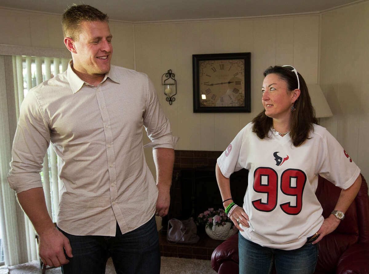 Houston Texans defensive end J.J. Watt, left, stands with contest winner Cody Beavers, right, as he arrives to deliver pizza for a pizza party on Tuesday, Oct. 28, 2014, in Houston. Every week throughout the Texans season, Papa John's of Houston will donate 10 percent of all Tuesday sals to the J.J. Watt Foundation, with Watt making special deliveries to a selected contest winner. ( Brett Coomer / Houston Chronicle )