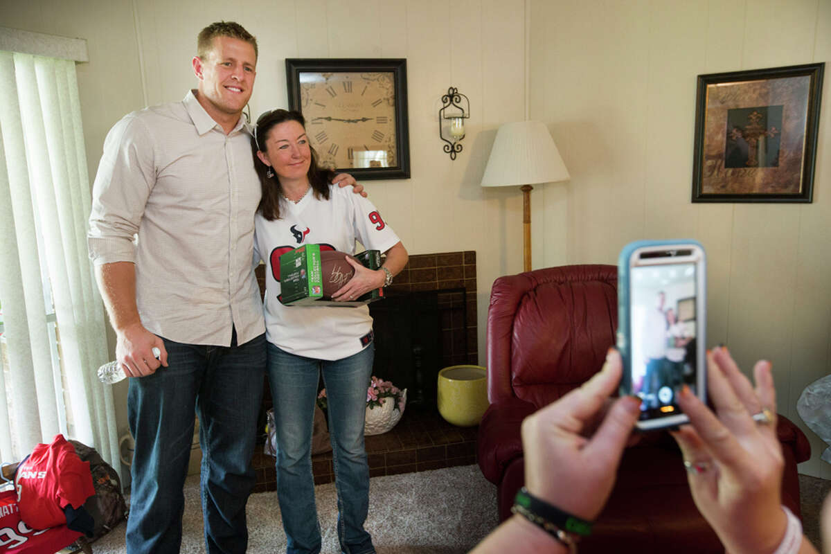 Houston Texans defensive end J.J. Watt, left, poses for a photo with contest winner Cody Beavers, right, as he arrives to deliver pizza for a pizza party on Tuesday, Oct. 28, 2014, in Houston. Every week throughout the Texans season, Papa John's of Houston will donate 10 percent of all Tuesday sals to the J.J. Watt Foundation, with Watt making special deliveries to a selected contest winner. ( Brett Coomer / Houston Chronicle )