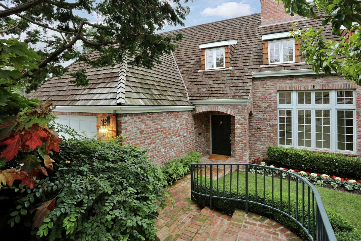 A brick walkway leads to the two-level home that features an exterior of brick and wooden shingles.