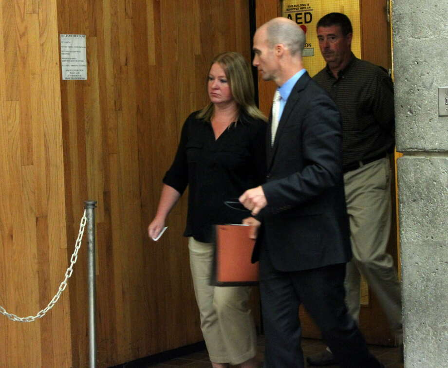 Carrie LaFond of Schenectady is led out of the Schenectady courthouse by her attorney James Knox, right, and followed by her husband, Paul LaFond Thursday, July 17, 2014, in Schenectady, N.Y. Carrie was a trusted accountant at John D. Marcella & Son Appliances & Home Entertainment who admitted she embezzled from the company. (Selby Smith/Special to the Times Union/archive)