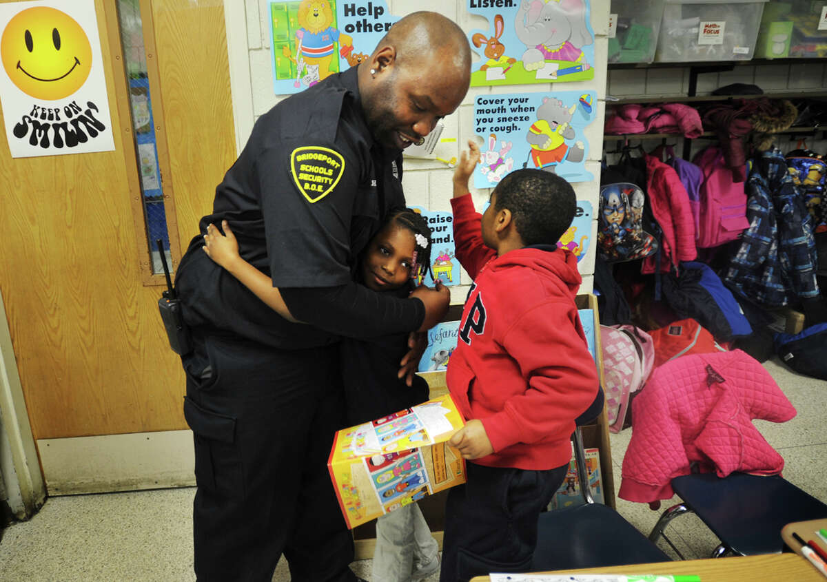 """Curiale School security guard Harry Bell receives hugs from second graders Tatyana Garner and Mario Shady, both 7, after passing out copies of his coloring book, """"Color a Positive Thought"""", at the school on Tuesday, November 25, 2014."""