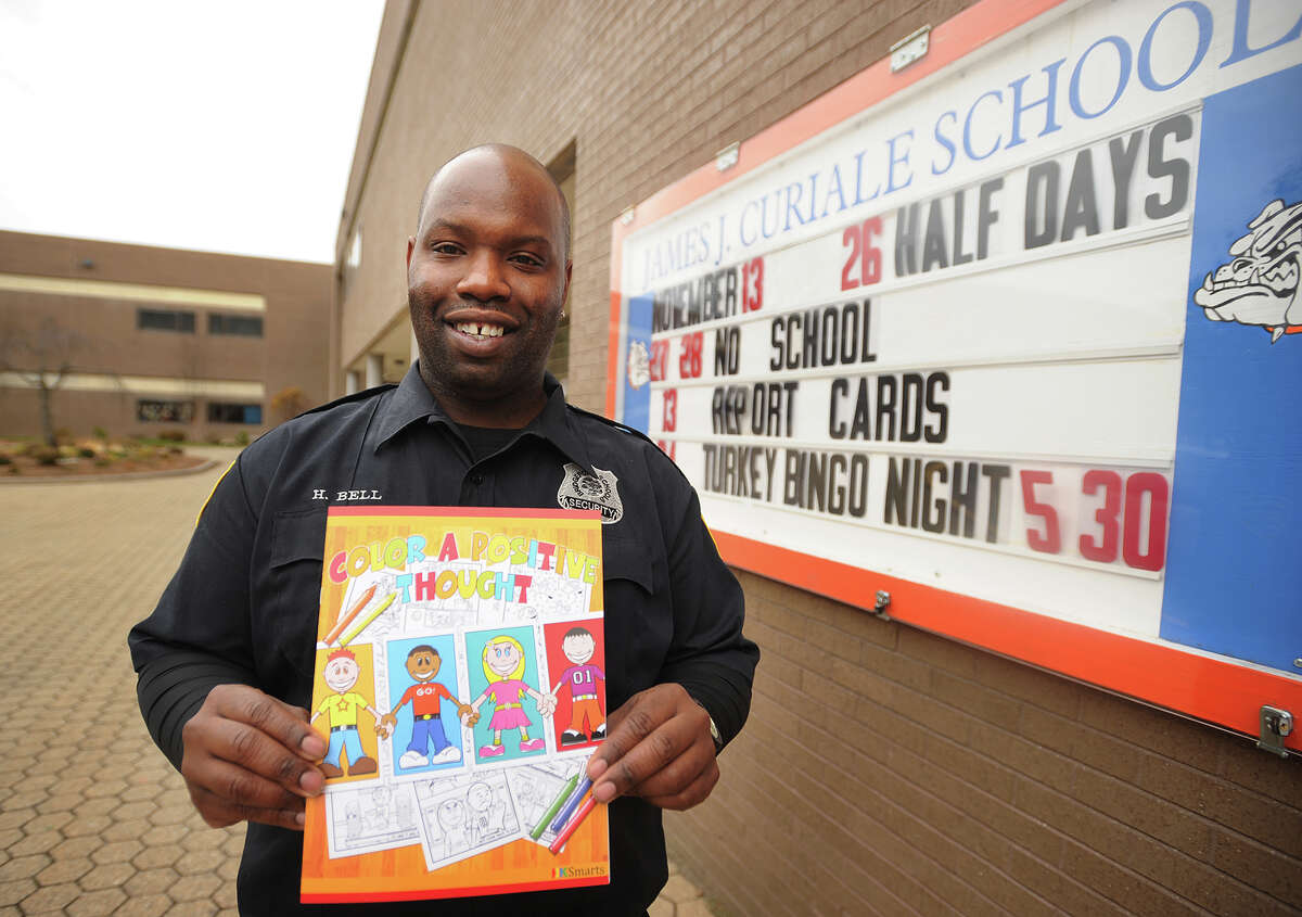 """Curiale School security guard Harry Bell with the coloring book he authored, """"Color a Positive Thought"""", outside the school in Bridgeport, Conn. on Tuesday, November 25, 2014."""