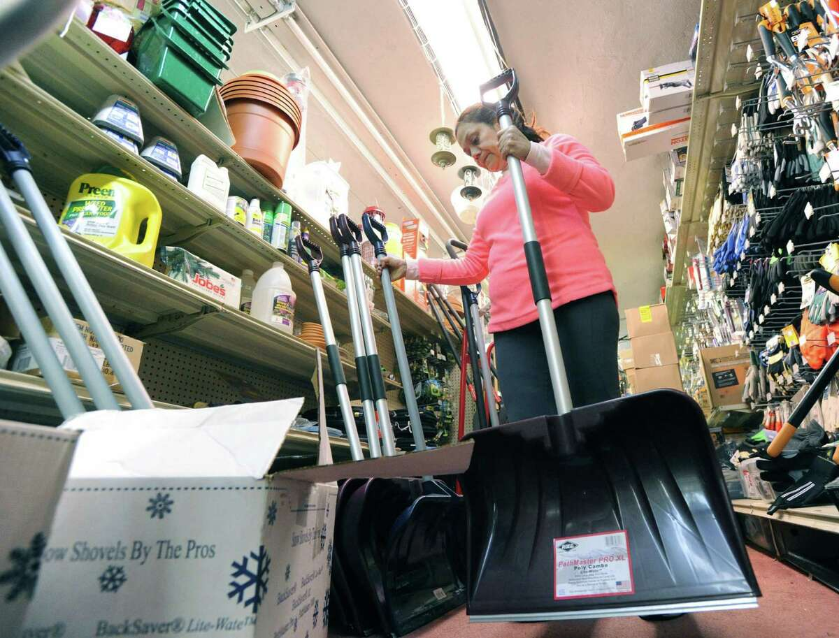 Rosario Gomez, a Greenwich Hardware store employee, stacks newly arrived shovels inside the store in Greenwich, Conn., Tuesday, Nov. 25, 2014.