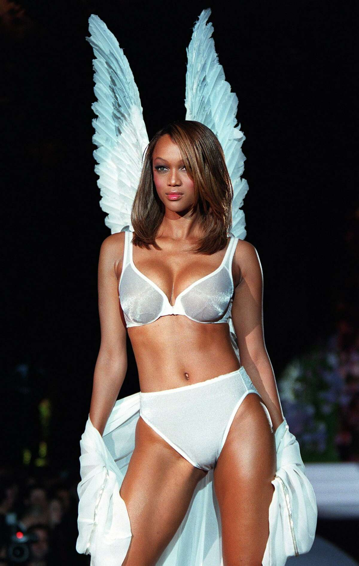 Model Tyra Banks wears a white Angel bra and matching panties with white Angel wings during the Victoria's Secret Spring 1998 Fashion show 03 February in New York. AFP PHOTO/Jon LEVY