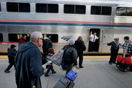 Passengers at the Martinez Amtrak Station rush to their Zephyr train, though often they get sidetracked and wait while freight trains get the right-of-way.