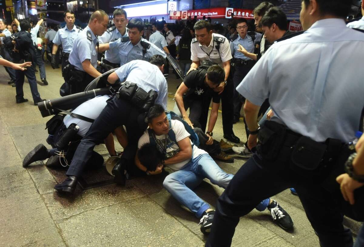 Police arrest a protester as they try to clear a road at a pro-democracy protest site Hong Kong.