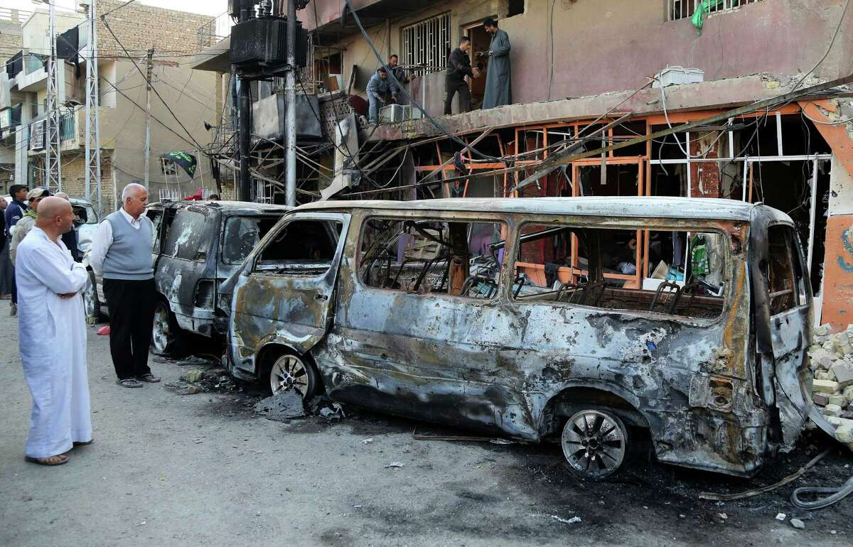 Civilians inspect the site of a car bomb in Baghdad's Gorayaat neighborhood.