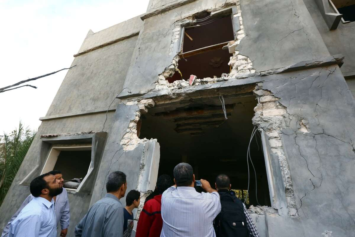Libyans gather next to a house damaged during an air strike by forces loyal to Libya's government near Tripoli's airport, held by anti-government militias.