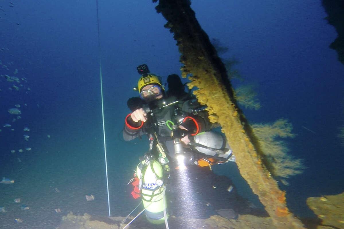 In this Jan. 25, 2014 image from video provided by Definitive Productions, diver Sandy Varin examines the underwater shipwreck of the S.S. Ventnor near Whangarei, off the northern New Zealand coast. The S.S. Ventnor sank 112 years ago off the northern New Zealand coast, bearing the exhumed bodies of 499 Chinese miners. They had tried their luck in New Zealand's gold rush, and had paid in advance to ensure their bodies would go back to China, no matter what. The wreck was discovered in 2012, raising the possibility that someday, the remains might go home.