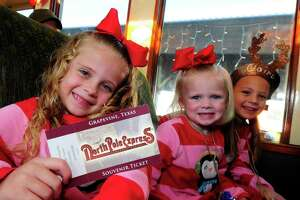 Children ride in decorated Victorian rail coaches aboard Grapevine's North Pole Express.