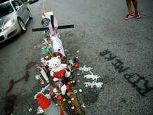 FILE - In this Monday, Aug. 11, 2014, file photo, a makeshift memorial sits in the middle of the street where 18-year-old Michael Brown was shot and killed by police, in Ferguson, Mo. By almost all accounts, Brown was engaged in some sort of physical struggle with Ferguson police Officer Darren Wilson just moments before he was fatally shot. That confrontation, perhaps more than anything, may help explain why grand jurors ultimately decided not to indict Wilson for killing Brown.